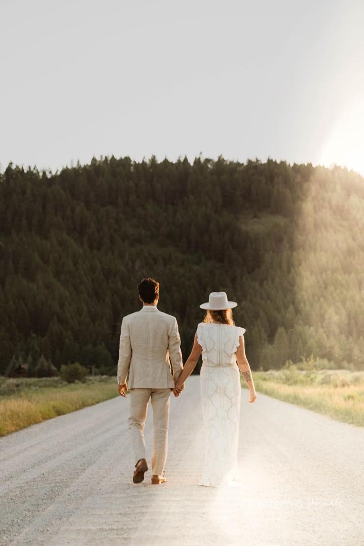 Bride and groom walk down dirt road at Moose Creek Ranch